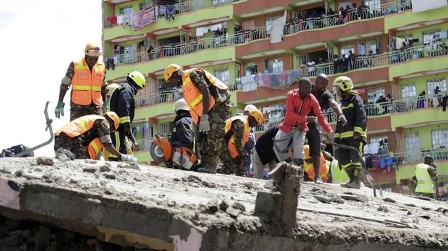 Masyarakat yang penasaran berdiri di sekitar bangunan enam lantai yang roboh di Nairobi saat tim SAR melakukan pencarian korban, Jumat (6/12). (AP Photo/Khalil Senosi)