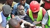 Tim SAR membopong seorang laki-laki yang terluka akibat runtuhan bangunan enam lantai yang terjadi di Kenya, Jumat (6/12).(AFP/Simon MAINA)