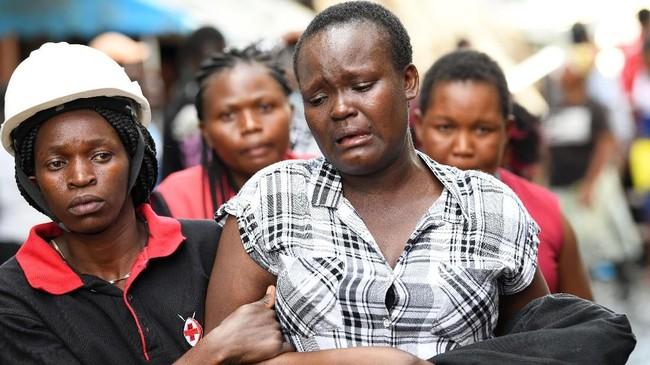 Seorang pekerja medis mendampingi seorang wanita yang sedang menangis di sekitar reruntuhan bangunan enam lantai yang roboh di Kenya, Jumat (6/12). (AFP/Simon MAINA)
