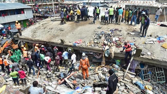 Masyarakat yang penasaran berdiri di sekitar bangunan enam lantai yang roboh di Nairobi saat tim SAR melakukan pencarian korban, Jumat (6/12). (AFP/Simon MAINA)