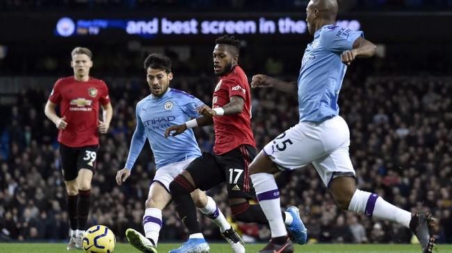 Gelandang Manchester United Fred, dikepung dua pemain Manchester City David Silva dan Fernandinho dalam laga yang berakhir 2-1 untuk kemenangan The Red Devils di Stadion Etihad, Sabtu (7/12) waktu setempat. (AP Photo/Rui Vieira)