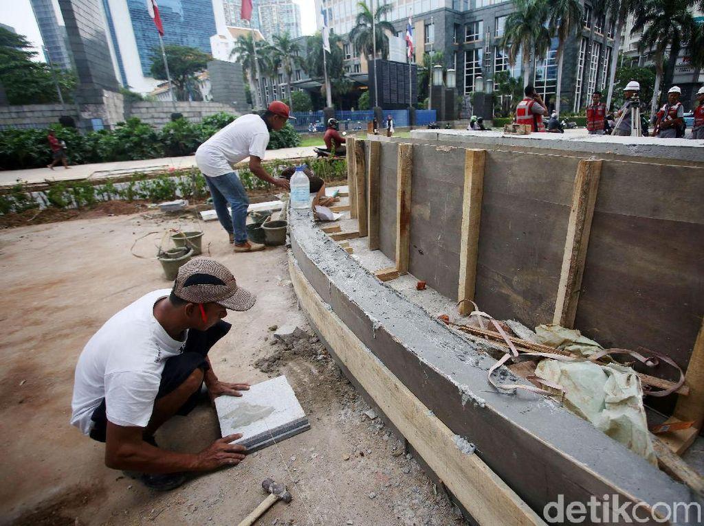 Dua orang pekerja sedang merampungkan pembangunan konstruksi amphiteater.