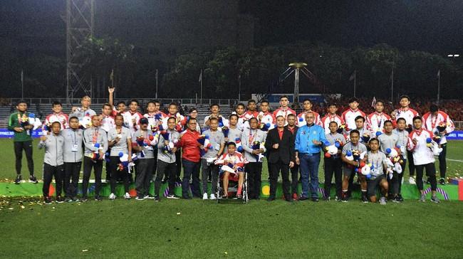 Para pemain Timnas U-22 Indonesia, termasuk Evan yang berada di atas kursi roda, beserta ofisialberpose seusai meraih perak sepak bola putra SEA Games 2019 di Stadion Rizal Memorial, Manila. (ANTARA FOTO/Sigid Kurniawan/pd)