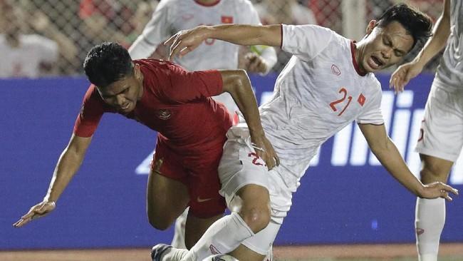 Nguyen Duc Chien (kanan) berebut bola dengan Asnawi Mangkualam. Laga berlangsung cukup keras lantaran wasit Majed Mohammed Alshamrani kerap abai dengan duel fisik yang melibatkan pemain dari kedua kubu. (AP Photo/Aaron Favila)