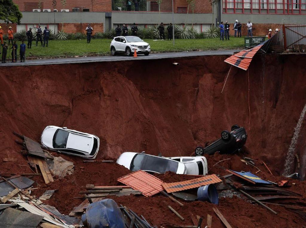 Tampak jalan raya tinggal setengah, karena setengahnya amblas ke tanah. AP Photo/Eraldo Peres.
