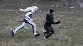 Para 'setan' memakai topeng buatan sendiri dari kulit domba dan bepergian dengan makhluk putih yang mewakili kematian dengan membawa sabit. (AP Photo/Petr David Josek)