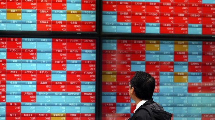 A man looks at an electronic stock board showing Japan's Nikkei 225 index at a securities firm in Tokyo Wednesday, Dec. 11, 2019. (AP Photo/Eugene Hoshiko)