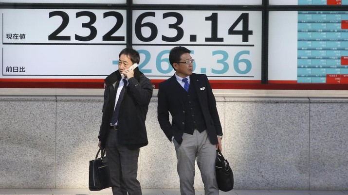 People stand in front of an electronic stock board of a securities firm in Tokyo, Tuesday, Dec. 3, 2019. Asian shares slipped Tuesday, following a drop on Wall Street amid pessimism over U.S.-China trade tensions. (AP Photo/Koji Sasahara)