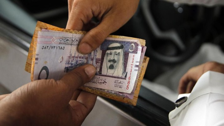 A station attendant returns Saudi Riyal cash to customer after he refuels his car at a gas station in Riyadh, Saudi Arabia, Monday, Dec. 9, 2019. (AP Photo/Amr Nabil)