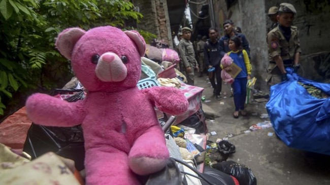 Warga hanya bisa pasrah saat rumah mereka dihancurkan dengan alat berat. Tanpa seorang anak membawa boneka miliknya saat penggusuran permukiman Tamansari di Bandung. (ANTARA FOTO/Raisan Al Farisi)