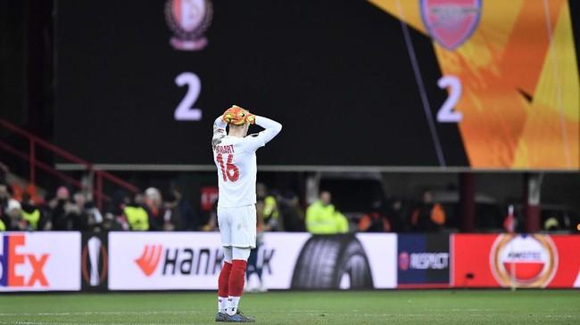Kiper Standard Liege Arnaud Bodart bereaksi setelah ditahan imbang Arsenal. Hasil ini membuat Arsenal menjadi juara Grup F dan lolos bersama Eintracht Frankfurt. (JOHN THYS / AFP)