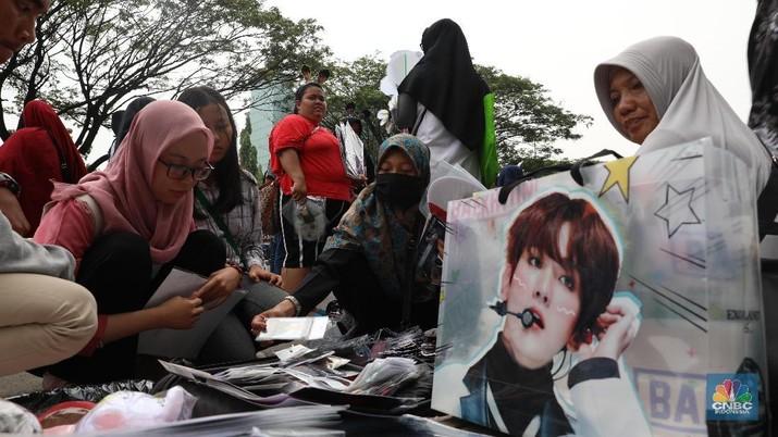 Sebelum nonton aksi idolanya, fans EXO berburu merchandise yang dijual di depan Trans Studio Cibubur.