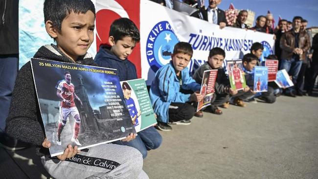 Bocah muslim Uighur memegang poster dukungan untuk Mesut Ozil. Mantan pemain Real Madrid itu dikecam netizen China karena mengungkapkan dukungan untuk etnis muslim Uighur. (Ozan KOSE / AFP)