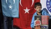 Seorang bocah pendukung muslim Uighur berdiri di depan bendera Turki dan Turkestan Timur sambil memegang poster dukungan untuk Mesut Ozil. (Ozan KOSE / AFP)
