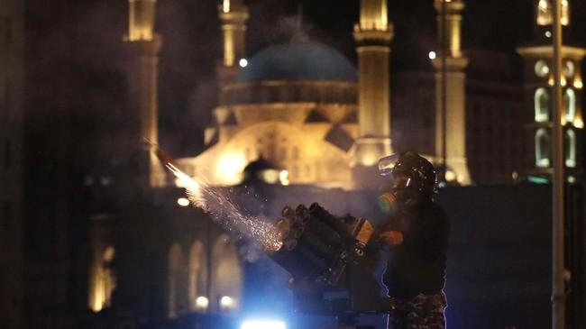 Polisi dilaporkan dilempari botol air minum dan petasan saat menjaga gedung parlemen yang menjadi titik kumpul pedemo.(AP Photo/Hussein Malla)