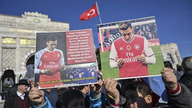 Pendukung muslim Uighur memegang poster foto gelandang Arsenal Mesut Ozil saat menggelar aksi damai di Beyazid Square, Istanbul, Sabtu (14/12). (Ozan KOSE / AFP)
