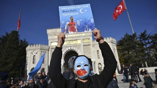 Seorang pendukung muslim Uighur di China memegang poster dukungan untuk Mesut Ozil bertuliskan,
