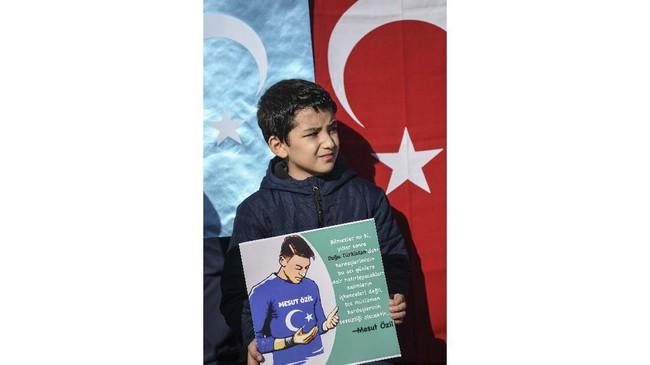 Bocah pendukug muslim Uighur membawa poster gambar Mesut Ozil. Dalam sebuah cuitan Ozil mengkritik negara-negara Islam yang dianggap tidak peduli terhadap nasib etnis Uighur. (Ozan KOSE / AFP)