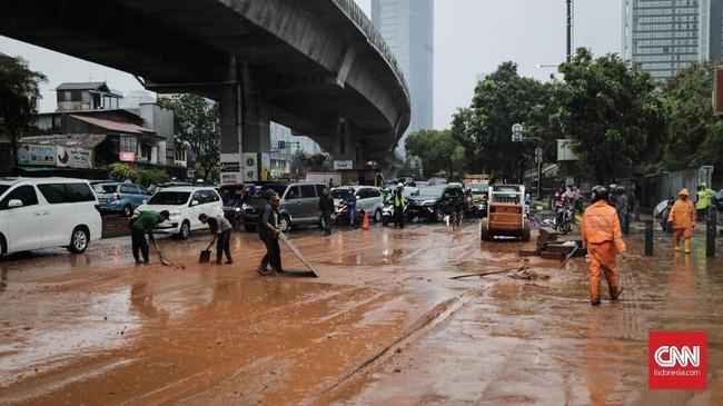 Petugas membersihkan endapan lumpur yang terbawa banjir di sekitar jalan dr susilo. Jakarta, Selasa, 17 Desember 2019. Hujan deras di sekitar Jakarta menyebabkan sejumlah genangan di jalan protokol. (CNNIndonesia/Adhi Wicaksono).
