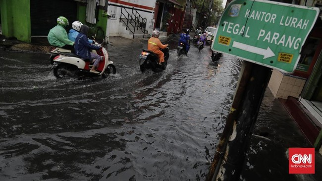 Warga melintasi genangan air akibat hujan deras di Tegal Parang, Jakarta, Selasa (17/12). (CNN Indonesia/Adhi Wicaksono
