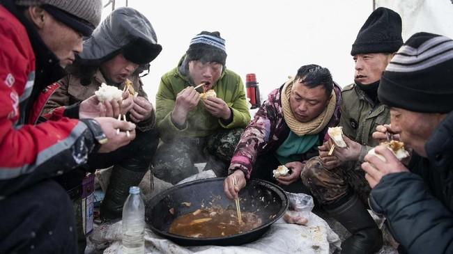 Para pekerja saat menikmati makan siang berupa ikan yang dipancing dari sungai.(NOEL CELIS / AFP)