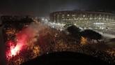 Polisi anti-huru hara bentrok dengan demonstran pada Rabu (18/12) malam di jalan dekat stadion Camp Nou saat laga Barcelona kontra Real Madrid. (AP Photo/Joan Mateu)