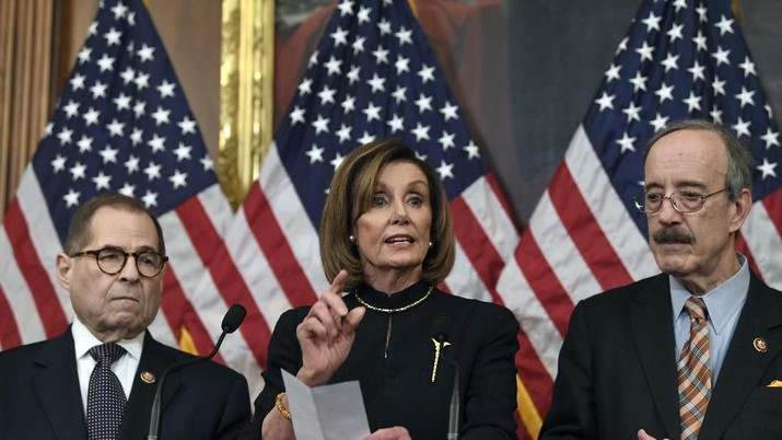 House Speaker Nancy Pelosi, D-Calif., speaks on Capitol Hill in Washington, Wednesday, Dec. 18, 2019, takes questions from reporters after the House of Representatives voted to impeach President Donald Trump on two charges, abuse of power and obstructing Congress, as House Judiciary Committee Chairman Rep. Jerrold Nadler, D-N.Y., and Chairman of the House Foreign Affairs Committee Eliot Engel, D-N.Y., listen. (AP Photo/Susan Walsh)