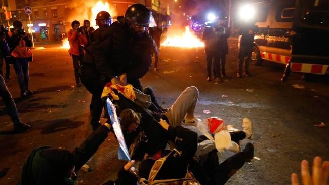 Pihak kepolisian mengatakan sembilan orang diamankan dan 12 orang terluka akibat bentrukan tersebut. (Photo by Pau Barrena / AFP)