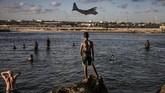 Para tentara menikmati hari libur, sementara warga Somalia melihat dari pantai di dekat pangkalan militer di Mogadishu. (AFP/Luis Tato)