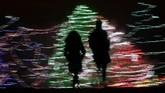 Bak lukisan, siluet warga terlihat di depan hiasan Natal di Lenexa, Kansas, AS. (AP Photo/Charlie Riedel)
