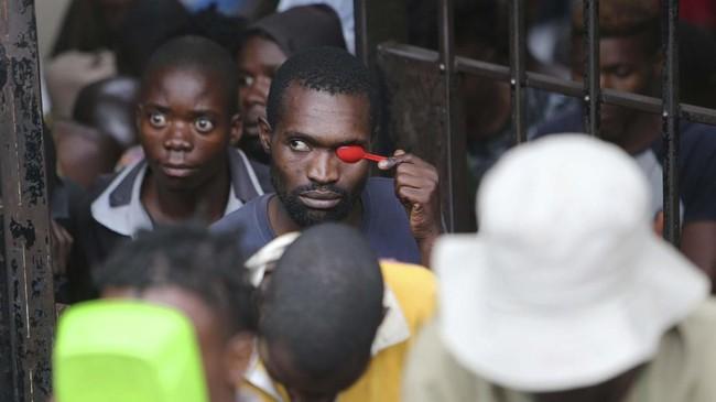 Seorang pria menutupi wajahnya dari bidikan kamera dengan sebuah sendok plastik ketika hadir di persidangan Marry Chiwenga, istri dari wakil presiden Zimbabwe, didakwa membunuh istrinya. (AP/Tsvangirayi Mukwazhi)