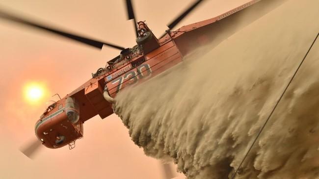 Aksi pemadaman juga didukung oleh tim pemadam AS dan Kanada serta personel dari Angkatan Pertahanan Australia. Namun, setegah dari kobaran api tetap tak terkendali. (Photo by PETER PARKS / AFP)