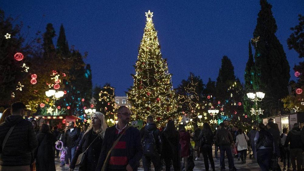 Orang-orang berjalan di depan gemerlap lampu pohon Natal di alun-alun Syntagma, Athena, Yunani. (AP Photo/Petros Giannakouris)