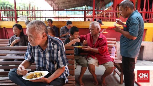 Tampak warga sekitar vihara tengah menikmati menu nasi kuning yang dijual di Warung Makan Podjok Halal vihara. CNNIndonesia/Safir Makki
