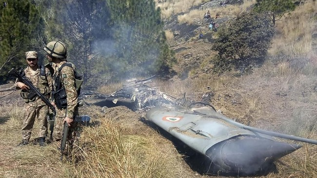 Tentara Pakistanberdiri di serpihan jet tempur India yang ditembak di Kashmir. (Photo by STR / AFP)