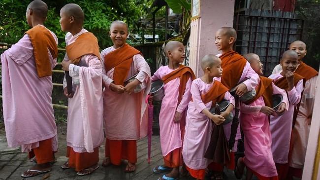 Dengan kepala plontos dibalut jubah merah muda, gadis-gadis biarawati Mingalar Thaikti duduk bersila di atas lantai kayu untuk berdoa. Mereka menguap dan berusaha menahan kantuk. (Ye Aung THU/AFP)