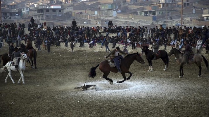 Afghan horse riders compete for the goat during a friendly buzkashi match on the outskirts of Kabul, Afghanistan, Friday, Dec. 27, 2019. Buzkashi is a traditional and the national sport of Afghanistan, where players compete to place a goat carcass into a goal circle. It was banned during the Taliban rule. (AP Photo/Rahmat Gul)