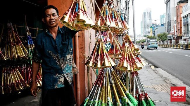 Sukani (46) membuat pluit bambu untuk terompet yang baru dibuatnya untuk perayaan tahun baru di kawasan Glodok, Jakarta Barat, Minggu (24/12/2019). CNN Indonesia/Andry Novelino
