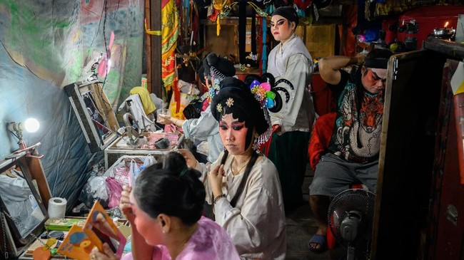 Rombongan opera Tionghoa ini berpindah dari jalan satu ke jalan yang lain selama berabad-abad. (Photo by Mladen ANTONOV / AFP)