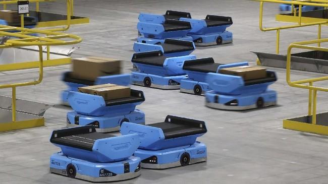 Robot-robot beroperasi di gudang Amazon, mengangkut paket-paket dari pekerja ke tempat pengiriman yang diatur berdasarkan kode pos. (AP Photo/Ross D. Franklin).