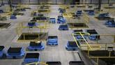 Puluhan robot menyalurkan paket-paket dari pekerja ke pengiriman. Amazon dan para pesaingnya semakin membutuhkan karyawan gudang yang terbiasa bekerja dengan robot. (AP Photo/Ross D. Franklin).
