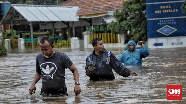 Warga melintas melewati luapan banjir akibat curah hujan tinggi di kawasan Hek, Jalan Raya Pondok Gede, Kramat Jati, Jakarta Timur, 1 Januari 2020. (CNN Indonesia/Bisma Septalisma)