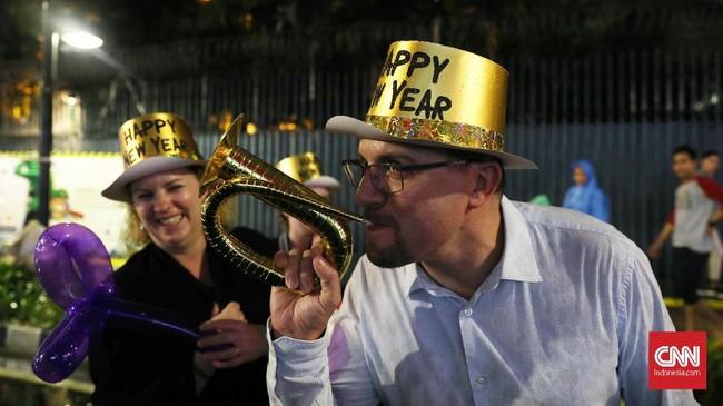 Wargamerayakan pergantian malam tahun baru 2020 dengan meniup terompet, menyalakan kembang api hingga menonton kembang api. (CNN Indonesia/Safir Makki).