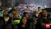 Beberapa warga tampak memakai jas hujan dan payung yang sebelumnya telah mereka siapkan. (CNN Indonesia/Safir Makki).