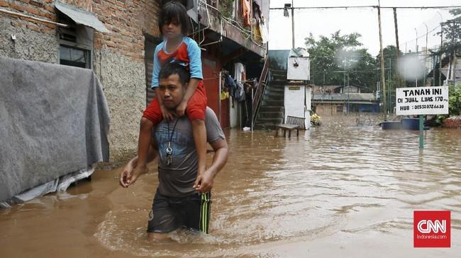 Seorang pria menggendong anak untuk dievakuasi mengungsi di kawasan rumah padat penduduk Rawajati, Kalibata, Jakarta Selatan, 1 Januari 2020. Banjir setinggi 2,5 meter merendam kawasan Rawajati. (CNN Indonesia/Andry Novelino)