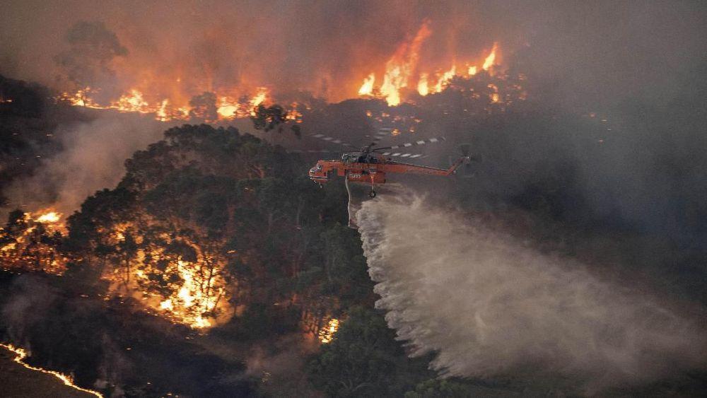 Sebuah helikopter menangani kebakaran hutan di East Gippsland, negara bagian Victoria, Australia. Kebakaran hutan yang membakar dua negara bagian berpenduduk terpadat di Australia menjebak warga kota tepi pantai dalam kondisi apokaliptik Selasa, (31/12/2019), dan dikhawatirkan telah menghancurkan banyak properti dan menyebabkan kematian.(Pemerintah Negara Bagian Victoria via AP)