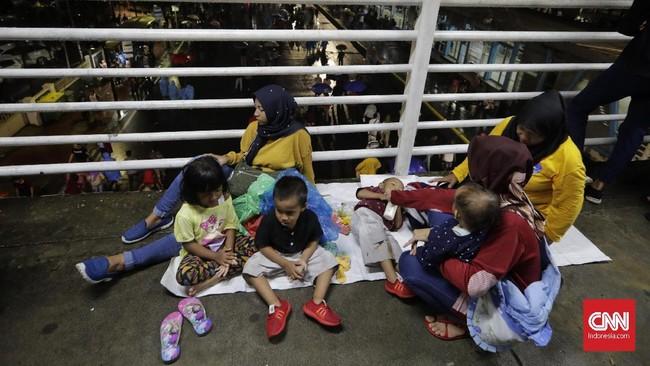 Sekitar pukul 16.15 WIB gerimis turun, beberapa orang berangsur bubar. Penonton yang tadinya menggelar tikar di trotoar pun bergegas membereskan barang bawaannya. Tetapi bagi mereka yang sudah berdiri tepat di depan panggung enggan beranjak dan memilih bertahan. (CNN Indonesia/Adhi Wicaksono).
