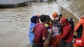 Petugas dan warga melakukan evakuasi saat banjir merendam daerah Cipinang Melayu, Jakarta, 1Januari 2020. (CNN Indonesia/Adhi Wicaksono)
