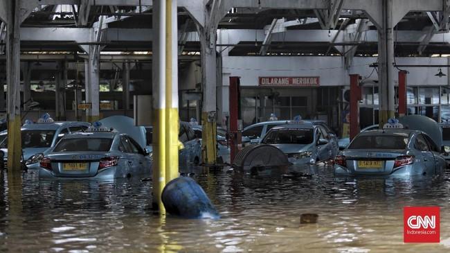 Banjir merendam mobil-mobil taksi di dalam pool milik Blue Bird di kawasan Hek, Jalan Raya Pondok Gede, Kramat Jati, Jakarta Timur, 1 Januari 2020. (CNN Indonesia/Bisma Septalisma)