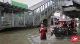 Warga menggunakan kereta kuda untuk melintasi banjir di kawasan sekitar Stasiun LRT Pulomas, Jakarta Timur, 1 Januari 2020.(CNN Indonesia/Adhi Wicaksono)